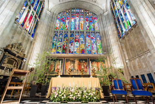 Nature-inspired summer meadow designs and birch trees at Stoke Place. Image by David Bostock Photography Blush and white meadow designs of roses, delphinium, ammi, alstromeria, astrantia, thlaspi, freesia and wild British foliages with birch trees at Eton College Chapel