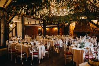 Reception hanging foliage and table garlands in barn