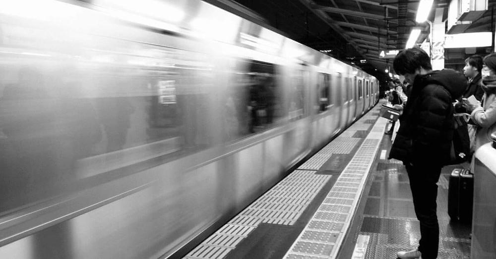 ภาพผู้โดยสารญี่ปุ่นที่กำลังรอรถไฟกำลังจอดที่ชานชะลา