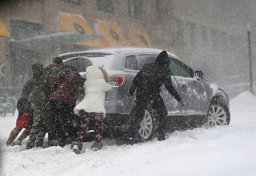 People pushing a car stuck in the snow