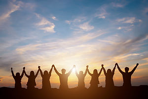 Silhouette of group happy business team making high hands over head in beautiful sunset sk