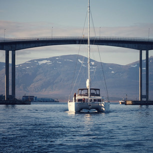sailing boat on the ocean with a bridge in the background