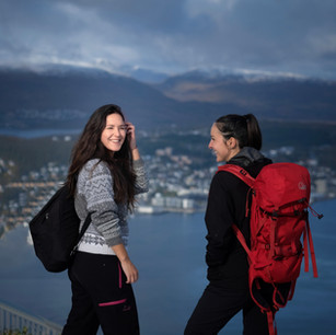 girls hiking with a city on the background