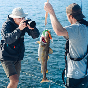 man holding a fish and taking a picture of it