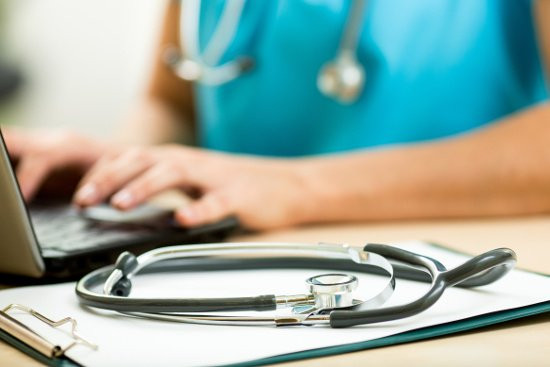 Doctor on Laptop next to Stethoscope on Clipboard