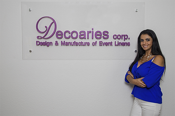 Nohelia Georges In Front Of Logo