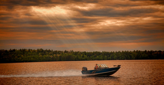 Godlight and fast running fishing boat on lake