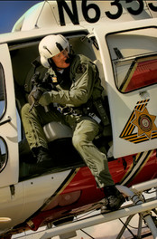 Police sharpshooter leans out of helicopter door