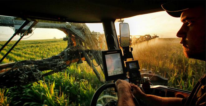 Operator sprays corn field from inside cab