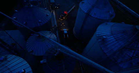 Farmers confer at night time grain bins during corn harvest