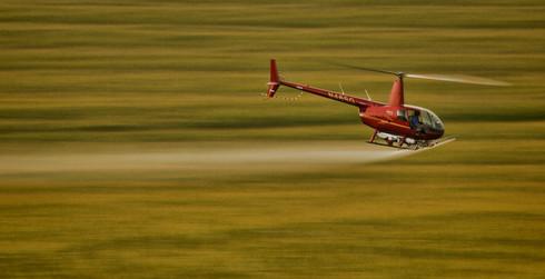Helicopter sprays corn field