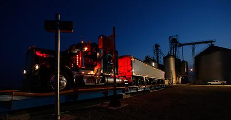Farm semi-truck weighs in at night at scales near grain bins