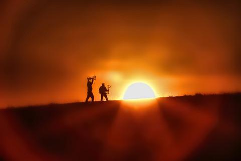 Jubilant archery hunters and sun