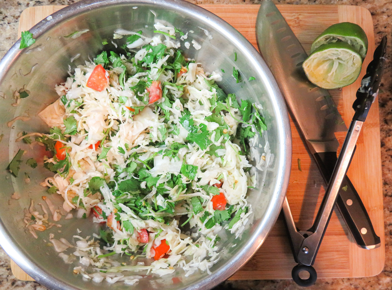 Ingredients mixed into a bowl including cilantro, cabbage, tomato, onion, and lime juice.