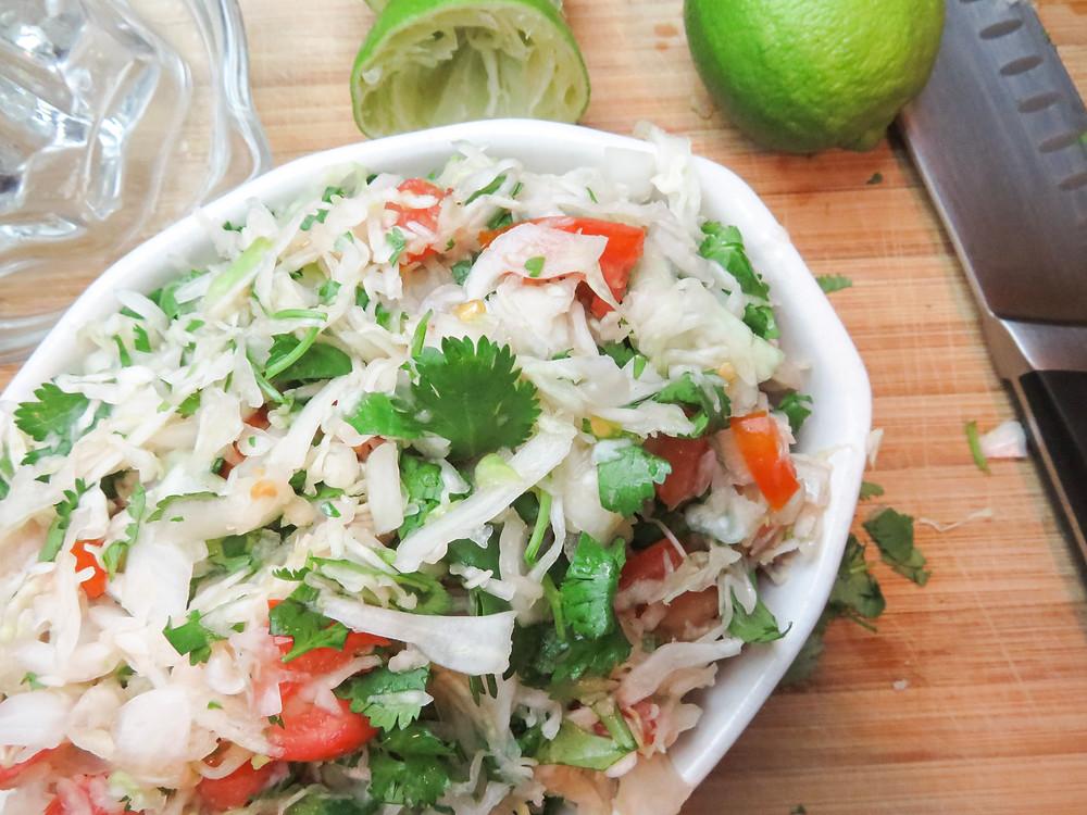Mexican slaw with cilantro, cabbage, onion & tomato.