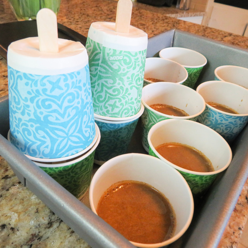 Coffee mixture poured into each cup. Cups are placed inside of a deep freezer safe baking pan.
