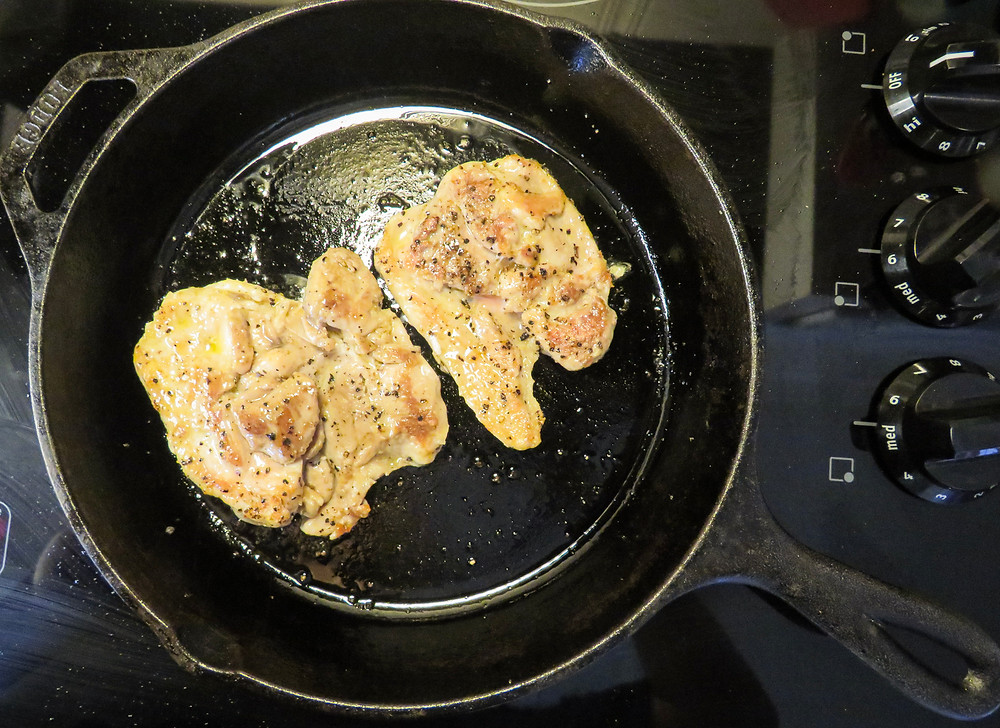 Chicken thighs cooked on one side in a cast iron skillet over the stove.