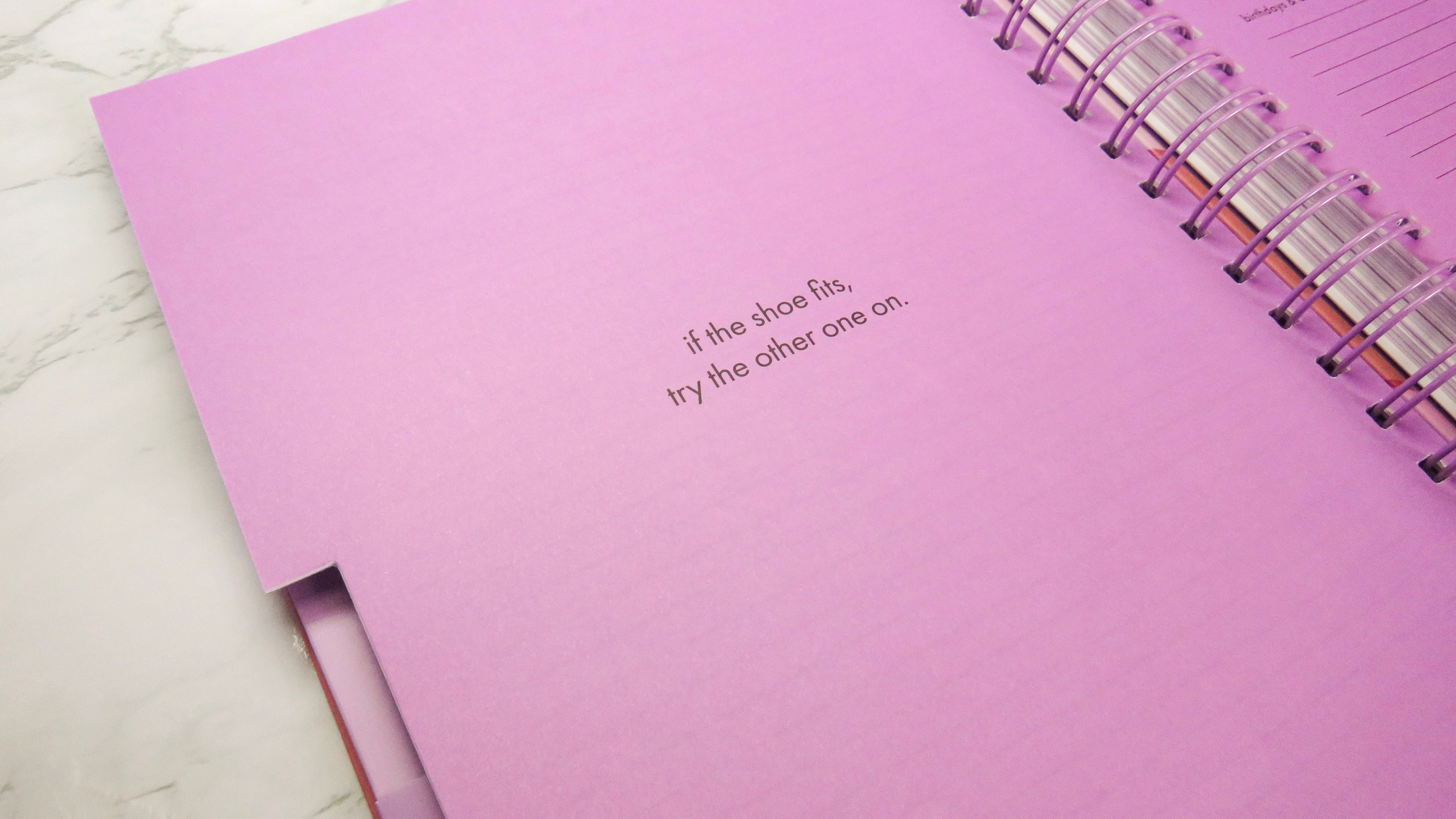 "Left side of a monthly tab divider with a quote: ""If the shoe fits, try the other one on"" in the Kate Spade New York planner."
