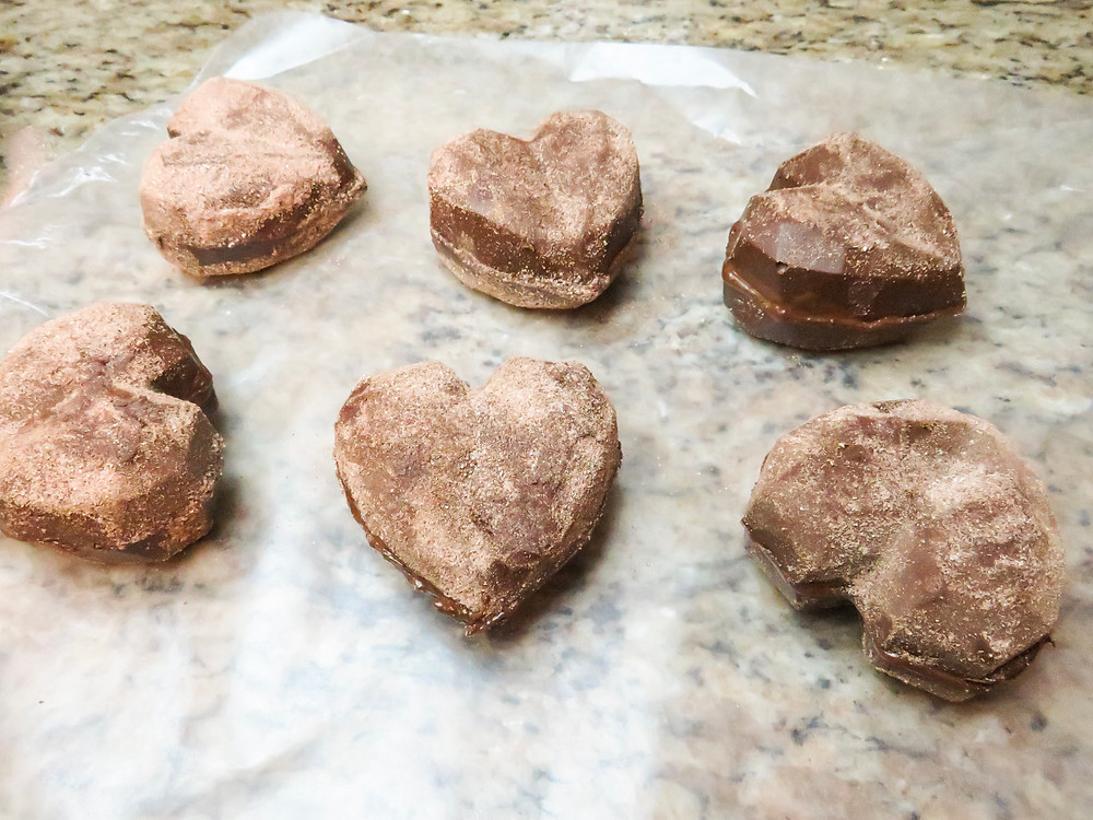 Heart shaped hot cocoa bombs on wax paper, ready to refrigererate.