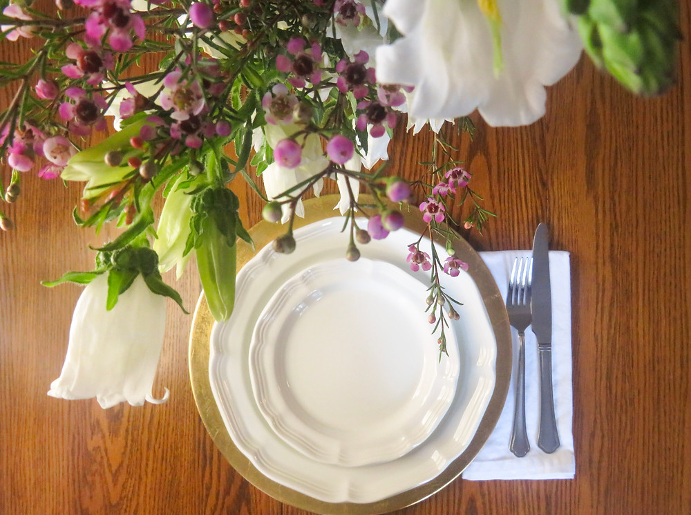 Looking down at a placesetting for dinner at a dining table with flowers hanging.