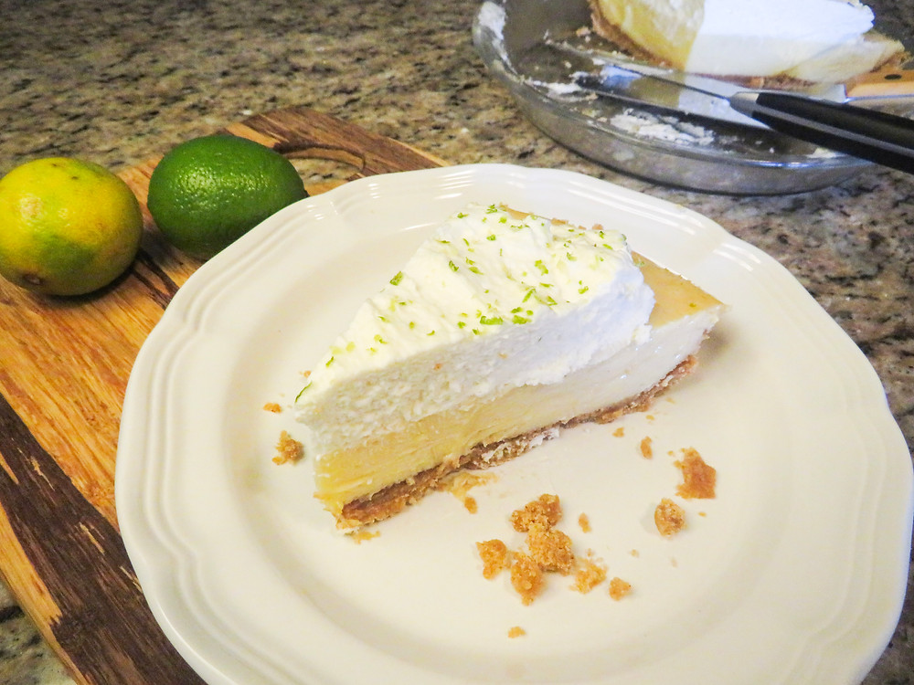 Large slice of key lime pie with graham cracker crumbs on the plate.