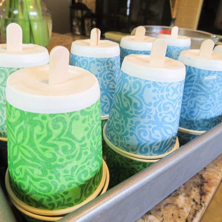 Paper cups topped with popsicle stick holder cups. Ready to put into the freezer.
