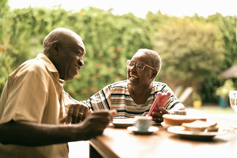 Elderly couple laughing over lunch