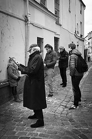 Fine Art black and white photography. Artist drawing portraits of tourists in the streets of Paris, France.