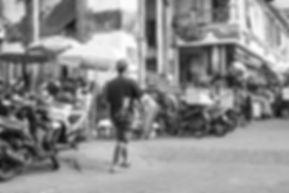 Black and white photograph of a man walking i Ubud, Bali.