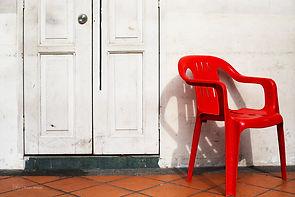 A red chair againts a white wall, minimalist print, Singapore