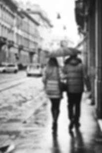 Black and white photograph of a couple walking, under the rain, in the streets of Milan, Italy.