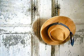 Photograph of an hat hanging on an old wooden door, in Franc