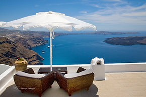 Photograph of two chairs and a umbrella on a roof above the sea, on the greek island of Santorini.