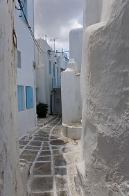 Photograph of a narrow white and blue street in the greek island of Mykonos.