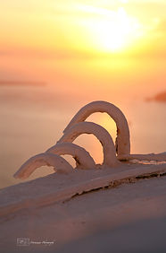 Photograph of the sunset above some architectural details in the greek island of Santorini.