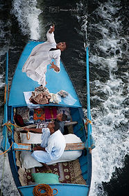 Egyptian men selling fabrics to tourists from their fast going boat, on the Nile river, Egypt.