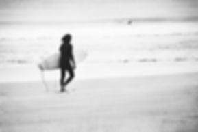 A surfer walking toward the ocean on Manly Beach,Sydney, Australia.