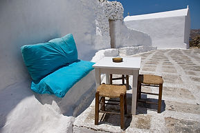 Photograph of a blue bench and a bar table in the middle of a white street, in the greek island of Mykonoss.