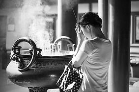 Black and white picture of a woman praying at the Buddha Tooth Relic Temple, Singapore.