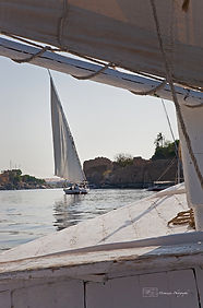 Photograph of a felucca, traditional sail boat on the Nile river in Egypt, with the city of Assouan in th background.