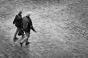 Black and white photograh of a couple walking their dog in Paris.