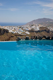 Photograph of a swimmig pool with a view on the greek island of Santorini.