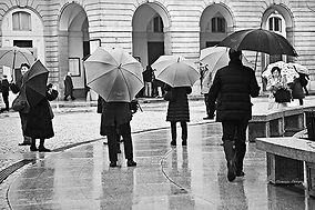 Black of white photograph of the Pizza della Scala in Milan, Italy, on a rainy day.