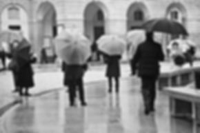 Black ad white photograph of a group of tourist holding umbrellas in Milan, Italy.