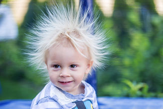 Cute little boy with static electricy ha