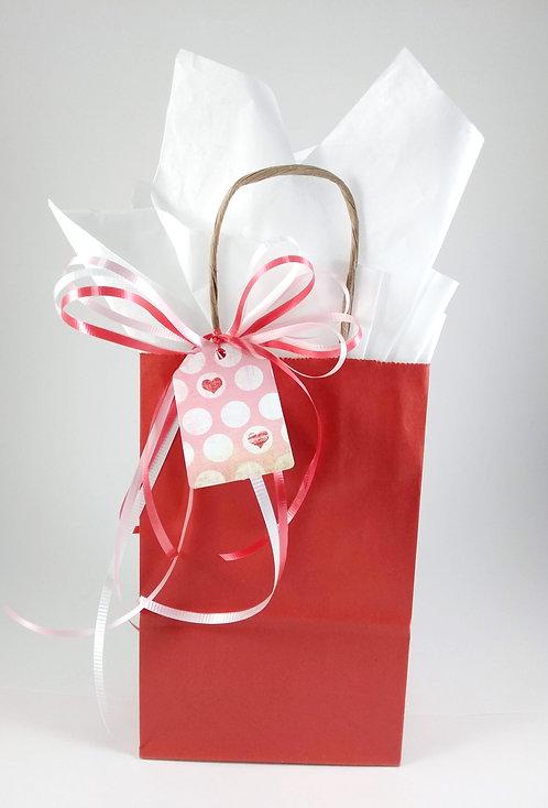 Emballage cadeau (sac rouge, papier blanc, boucles de ruban et étiquette)