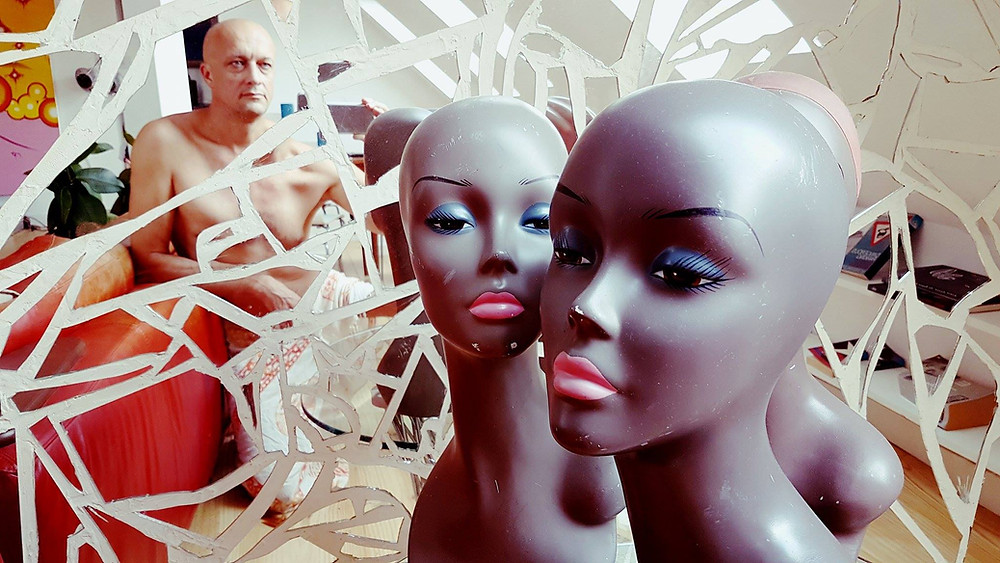 man looking at himself through a broken mirror of lies with mannequin heads with lifeless eyes.