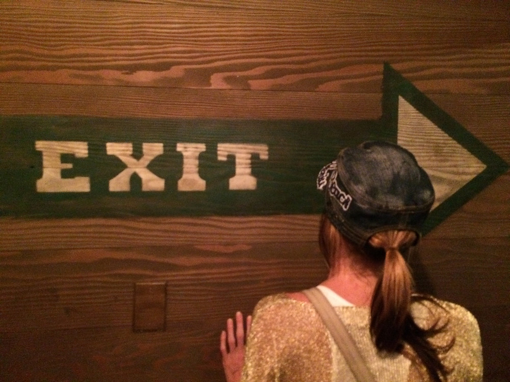Girl facing wall with words EXIT painted on green arrow pointing right