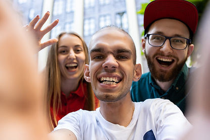 """Three young adults laughing in a city.  SDRC encourages you to """"share your story"""""""