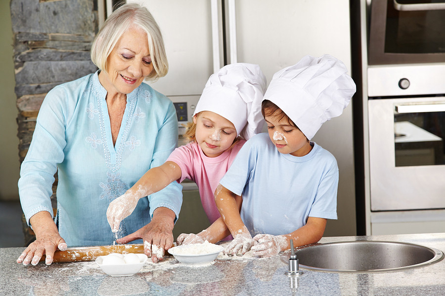 family using kitchen island with granite countertops to cook